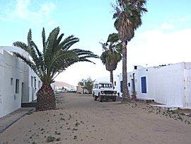 Zandwegen, witte huizen, blauwe kozijnen en landrovers, straatbeeld Graciosa