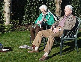 De eerste zonnestralen in NL, ouders van Ernie thee drinkend in de tuin