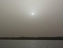De harmatan, woestijn wind met zand, maakt het mistig, zicht tot 200m. Op de foto staat de zon !