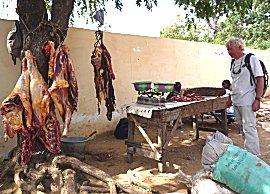 Erik koopt een mals stukje vlees bij de slager in Foundiougne