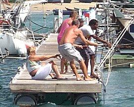 Op de steiger sleept men met man en macht een boot retour box