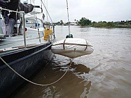 De bijboot hangen we 's-nachts boven het water zodat ie niet volloopt via de lekkende bodem.