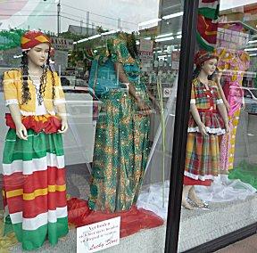 In de etalage traditionele kleding op de paspoppen.